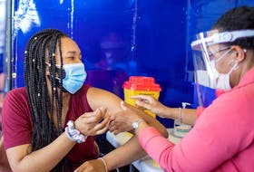A healthcare worker administers a Pfizer COVID-19 vaccine at a pop up clinic in Brampton, Ontario.