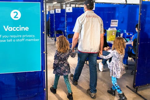 A man arrives with two young girls for his shot at a COVID-19 vaccination clinic in Toronto. Children under 12 are not yet being vaccinated and there is some debate among medical experts about the benefits of doing so.