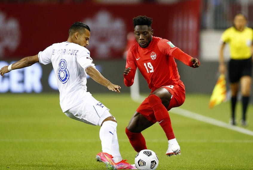 Alphonso Davies (19) of Canada battles for the ball against Edwin Rodriguez (8) of Honduras during their 2022 World Cup qualifying match at BMO Field on Sept. 2, 2021, in Toronto.