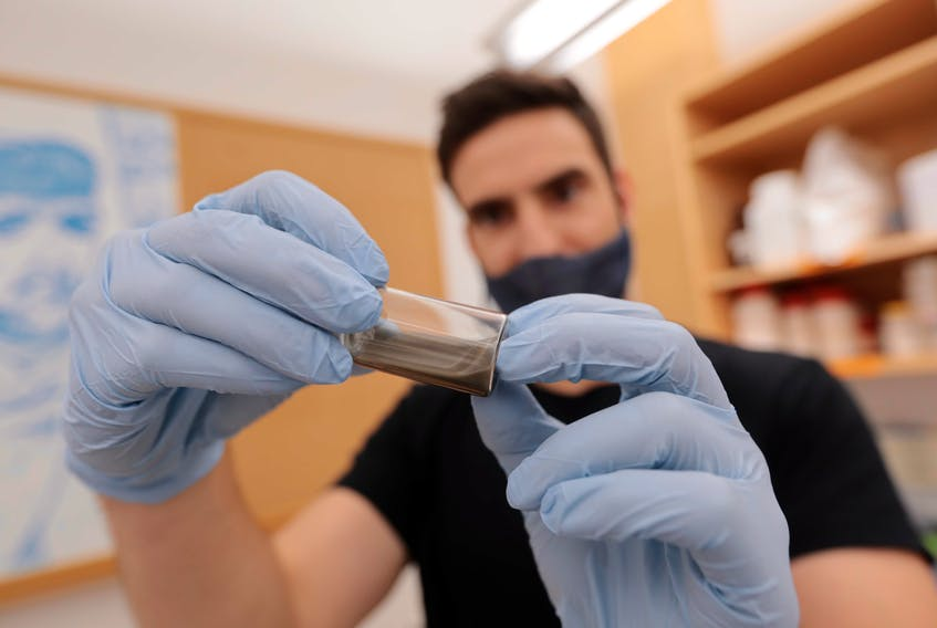 John Frampton, an associate professor at Dalhousie's School of Biomedical Engineering, holds a vial of polymer paste at his lab in Halifax. - Eric Wynne