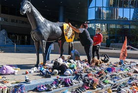 On Wednesday, September 29, 2021, Yvonne Henderson, left, and Auggie Hunter with Bear Clan Patrol Calgary attach a poster to one of the statues outside City Hall in preparation for September 30's vigil on National Day for Truth and Reconciliation.