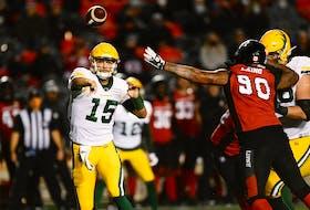 Edmonton Elks quarterback Taylor Cornelius (15) throws the ball past the arm of Ottawa Redblacks defensive lineman Cleyon Laing (90) in Ottawa on Tuesday, Sept. 28, 2021.