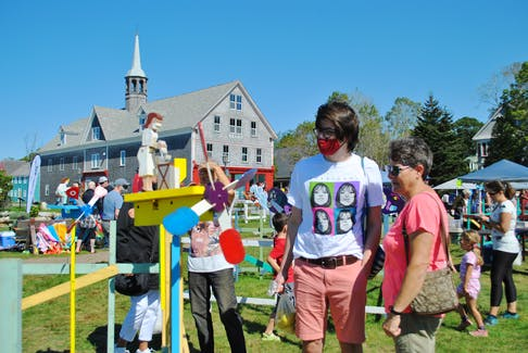 People stroll through the display at the 21st annual Whirligig and Weathervane Festival on Sept. 18 and 19 on the Shelburne waterfront. KATHY JOHNSON
