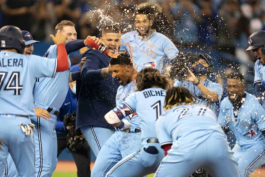 Toronto Blue Jays shortstop Marcus Semien celebrates with the team after hitting a walkoff home run during the ninth inning against the Oakland Athletics at Rogers Centre in Toronto, Sept. 3, 2021.