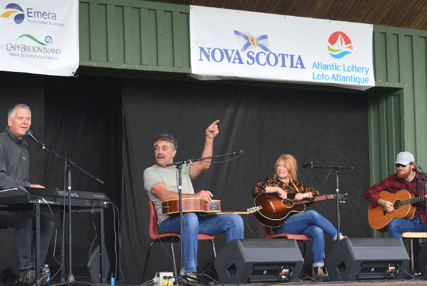 John Curtis Sampson, second from left, prompts the crowd to sing along with Kim Dunn, left, as Norma MacDonald and Jason MacDonald look on during a songwriters circle segments of the Acoustic Roots Festival on Sunday afternoon at Two Rivers Wildlife Park. — IAN NATHANSON/CAPE BRETON POST
