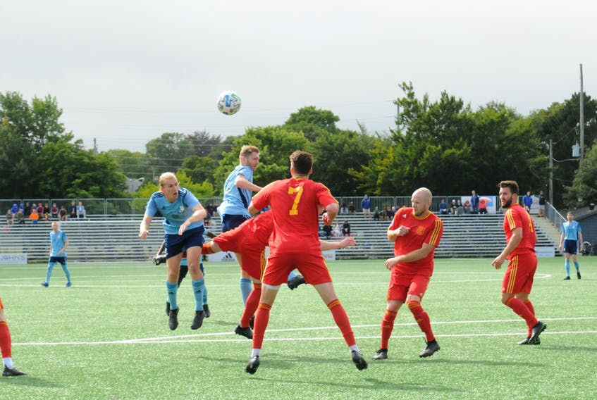 Feildians and Holy Cross players vie for an airborne ball near midfield during Sunday's Johnson Insurance Challenge Cup provincial men's soccer final at King George V Park in St. John's. Feildians prevailed 2-1 to take their first Challenge Cup crown since 1969. — Joe Gibbons/The Telegram