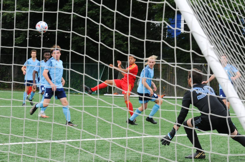 Owen Sheppard (centre) of Holy Cross takes a shot as Feildians goalkeeper Kyle Potter gets ready to make the save. — Joe Gibbons/The Telegram