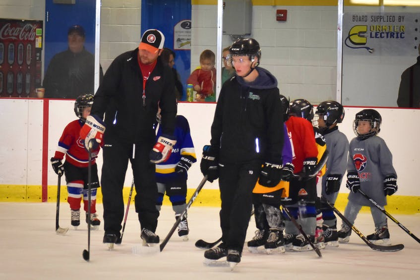 Coach Nathan Desroches with Alex Hutchinson, instructing kids during a practice. - Contributed