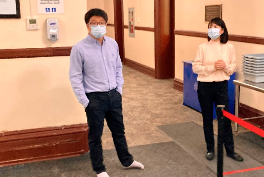Acupuncturist Xiao Han Li stands in the lobby of the Halifax provincial courthouse Tuesday with his mother, Qing Li, after arriving for the start of his trial on a charge of sexual assault.