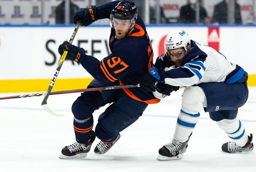 Edmonton Oilers' Connor McDavid (97) battles Winnipeg Jets' Dylan DeMelo (2) during the first period of NHL North Division playoff action at Rogers Place in Edmonton, on Wednesday, May 19, 2021. Photo by Ian Kucerak