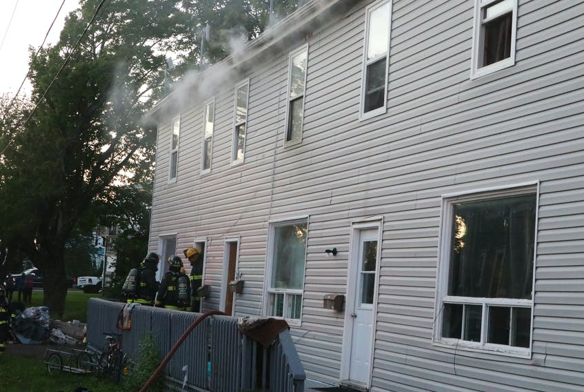 Smoke billows from the eves of a Gerard Avenue apartment building near downtown Amherst. Six adults and nine children in three units were left without shelter following the fire. Tom McCoag/Town of Amherst photo