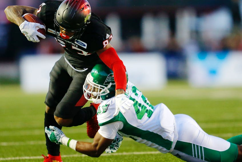 Saskatchewan Roughriders Derrick Moncrief tackles Calgary Stampeders ballcarrier Markeith Ambles at McMahon Stadium in Calgary on Oct. 20, 2018.