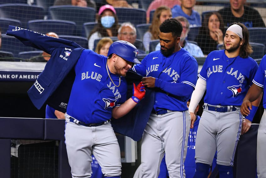 Blue Jays' Alejandro Kirk gets his home run jacket with help from Teoscar Hernandez as Bo Bichette looks on after Kirk hit a home run against the New York Yankees during the eighth inning of a game at Yankee Stadium on Wednesday, Sept. 7, 2021.