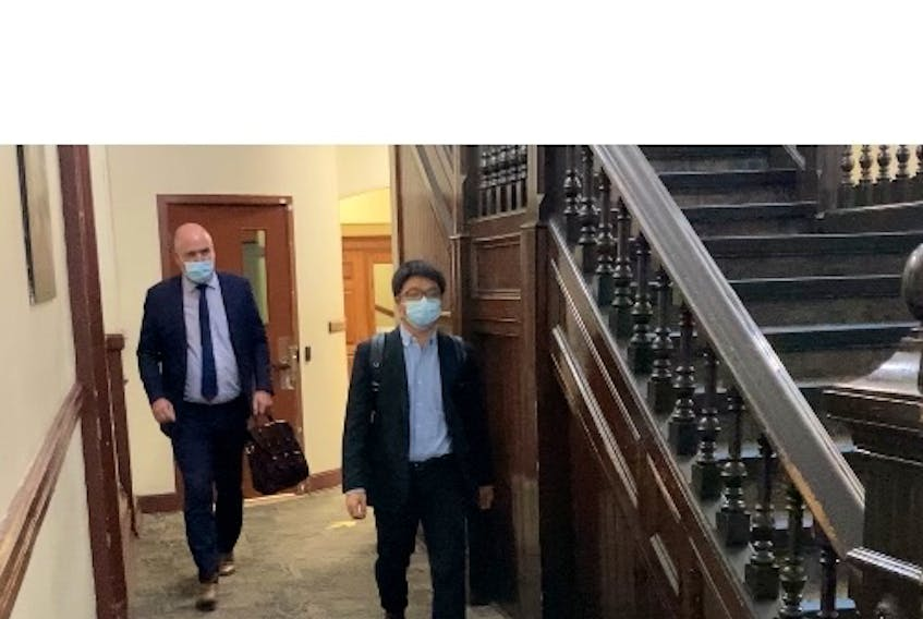 Halifax acupuncturist Xiao Han Li leaves court with lawyer Ian Hutchison on Thursday after his sexual assault trial, which got underway Tuesday, was adjourned to allow defence co-counsel Mark Knox to get a COVID-19 test.