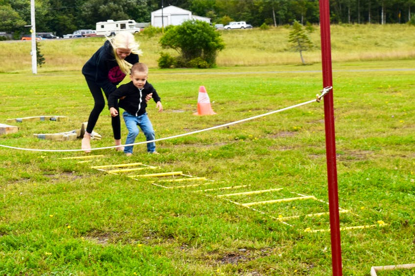 Saffron Slade helps Damian Slade through a kid's firefighter course set up as part of the Westville Canada Day Celebrations which had been postponed to the Labour Day weekend. - Adam MacInnis