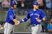 Blue Jays baserunners Jake Lamb, left, and Danny Jansen, right, slap hands after scoring on a single by Marcus Semien during the fourth inning of a game against the New York Yankees at Yankee Stadium in New York City, Wednesday, Sept. 8, 2021.