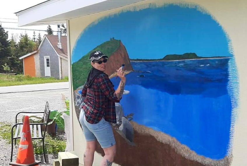 Yarmouth County resident Belinda Conrad paints a mural on the side of the Seaforth Treasure Chest gift shop building in Seaforth, in the Halifax Regional Municipality. The project is a labour of love for Conrad, whose best friend owns the business.