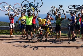 This file photo shows a participants in a previous annual Recovery Ride lifting their bikes above their heads at the top of MacKenzie Mountain on the Cabot Trail. The fundraiser, in its 18th year, has raised more than $50,000 for various Cape Breton charities and organizations. FILE PHOTO/CAPE BRETON POST
