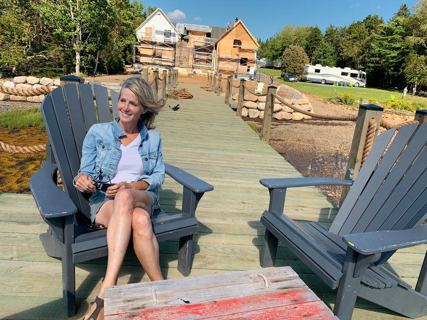 Kimberly Harrison sits on her new wharf with her house under construction in the background.  - Saltwire network