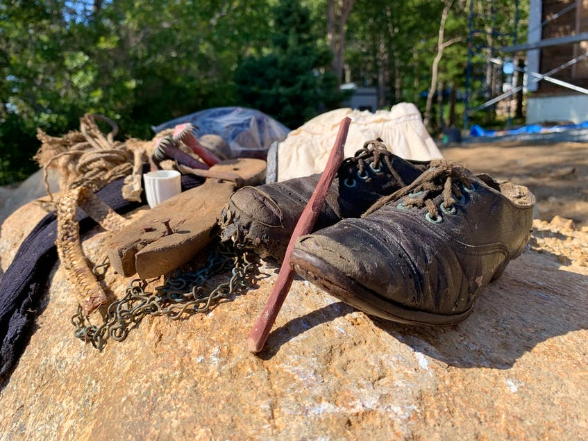 A collection of items found inside the walls of this East LaHave home. They include a wooden skate, a piece from a petticoat and shoes. - Jen Taplin