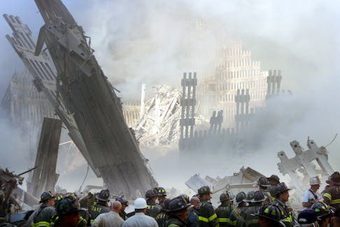 A group of firefighters stand on the street near the destroyed World Trade Centre in New York on September 11, 2001. REUTERS/Shannon Stapleton/File photo