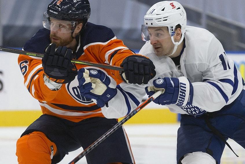 The Edmonton Oilers' Adam Larsson (6) battles the Toronto Maple Leafs' Zach Hyman (11) at Rogers Place in Edmonton on Saturday Feb. 27, 2021.