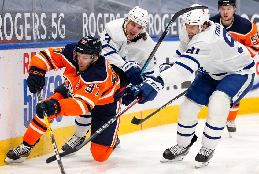 Edmonton Oilers' Connor McDavid (97) battles Toronto Maple Leafs' Justin Holl (3) and John Tavares (91) during third period NHL action at Rogers Place in Edmonton, on Monday, March 1, 2021.