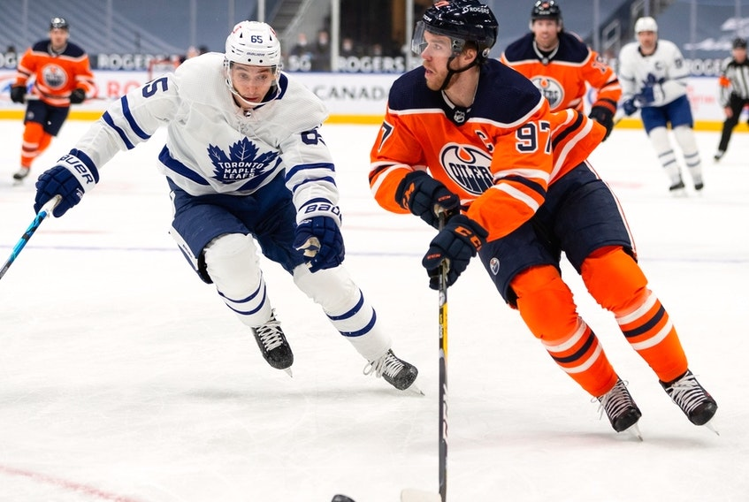 Edmonton Oilers captain Connor McDavid (97) is chased by the Toronto Maple Leafs' Ilya Mikheyev (65) at Rogers Place in Edmonton on Wednesday, March 3, 2021.