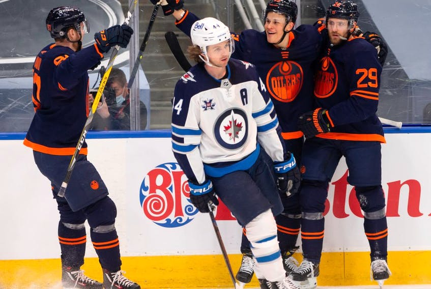Edmonton Oilers' Leon Draisaitl (29) celebrates a goal on Winnipeg Jets' goaltender Connor Hellebuyck (37) with teammates during third period NHL action at Rogers Place in Edmonton, on Saturday, March 20, 2021.