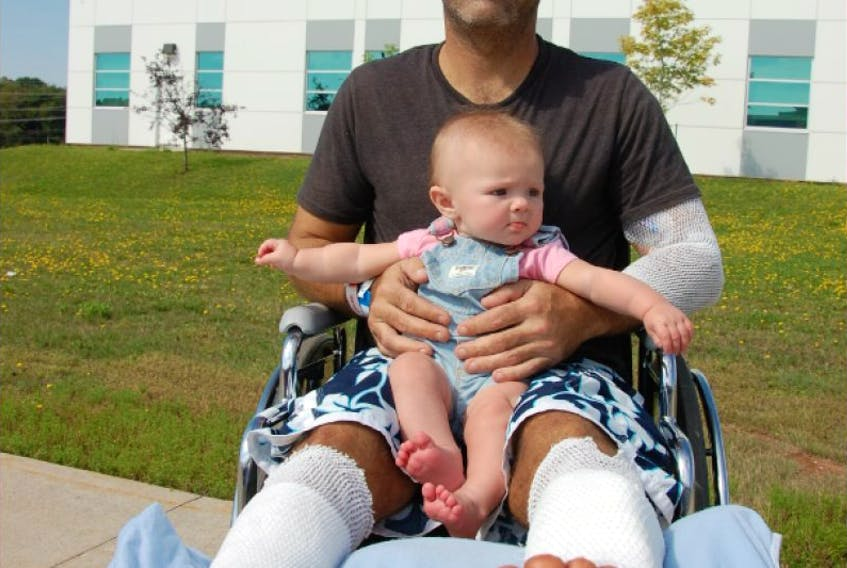 Bobby Gallant holds his daughter Sarah outside the Queen Elizabeth Hospital in Charlottetown.