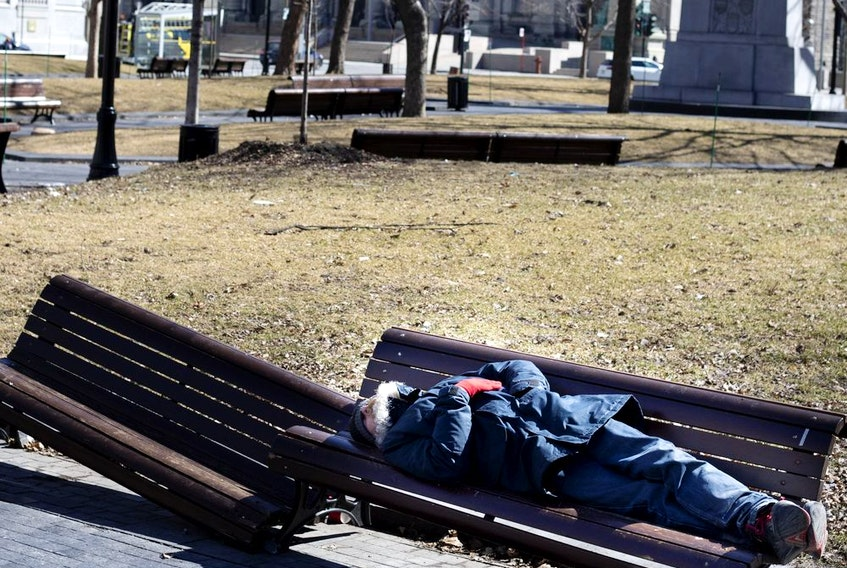 A homeless man sleeps on a bench in Dorchester Square as Montreal deals with the coronavirus crisis March 27, 2020.