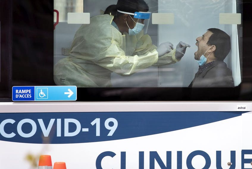 A health-care worker administers a test swab at a mobile COVID-19 testing site in Montreal on May 9, 2020.
