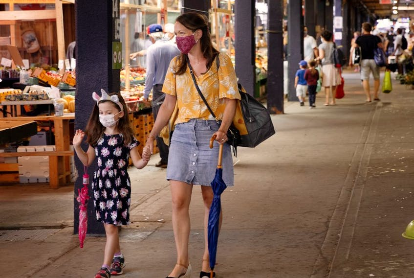 Marie-Helene Paquette and her daughter Romi stay out of the rain as they walk the Atwater Market in Montreal, on Sunday, August 2, 2020. (Allen McInnis / MONTREAL GAZETTE) ORG XMIT: 64812