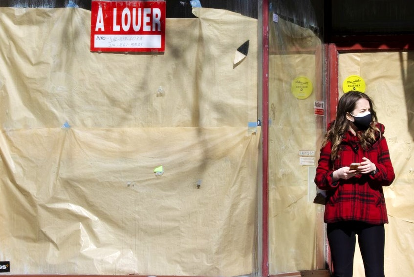 MONTREAL, QUE.: February 26, 2021 -- A woman stops to check her phone in front of a shuttered store on Saint-Laurent St. in Montreal Feb. 26, 2021.