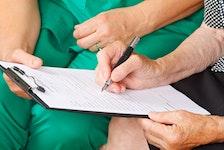 A patient signs a medical consent form.