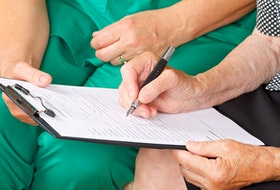 A patient signs a medical consent form.