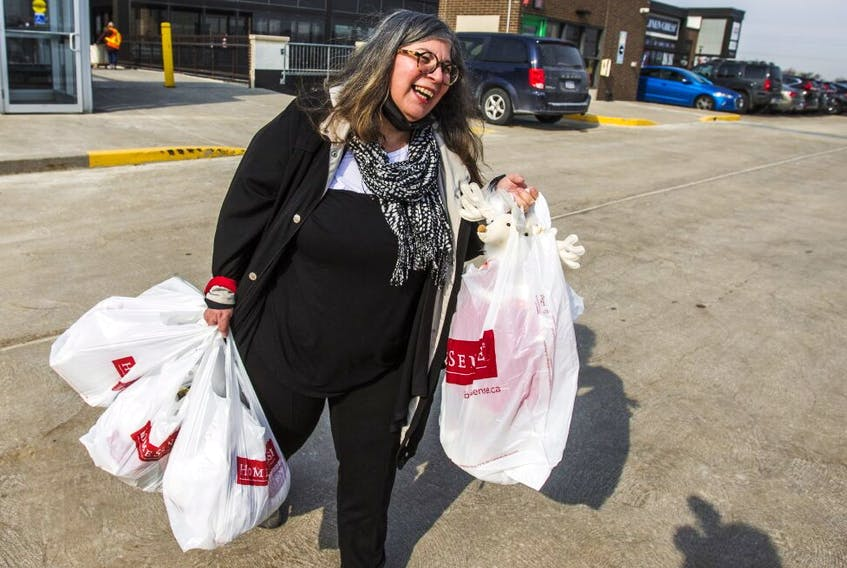 Rita DeMontis, the  Sun's senior national lifestyle and food editor, carries her haul to her car after  enjoying in-store shopping at the HomeSense at Stock Yards Village in Toronto, on March 8, 2021.