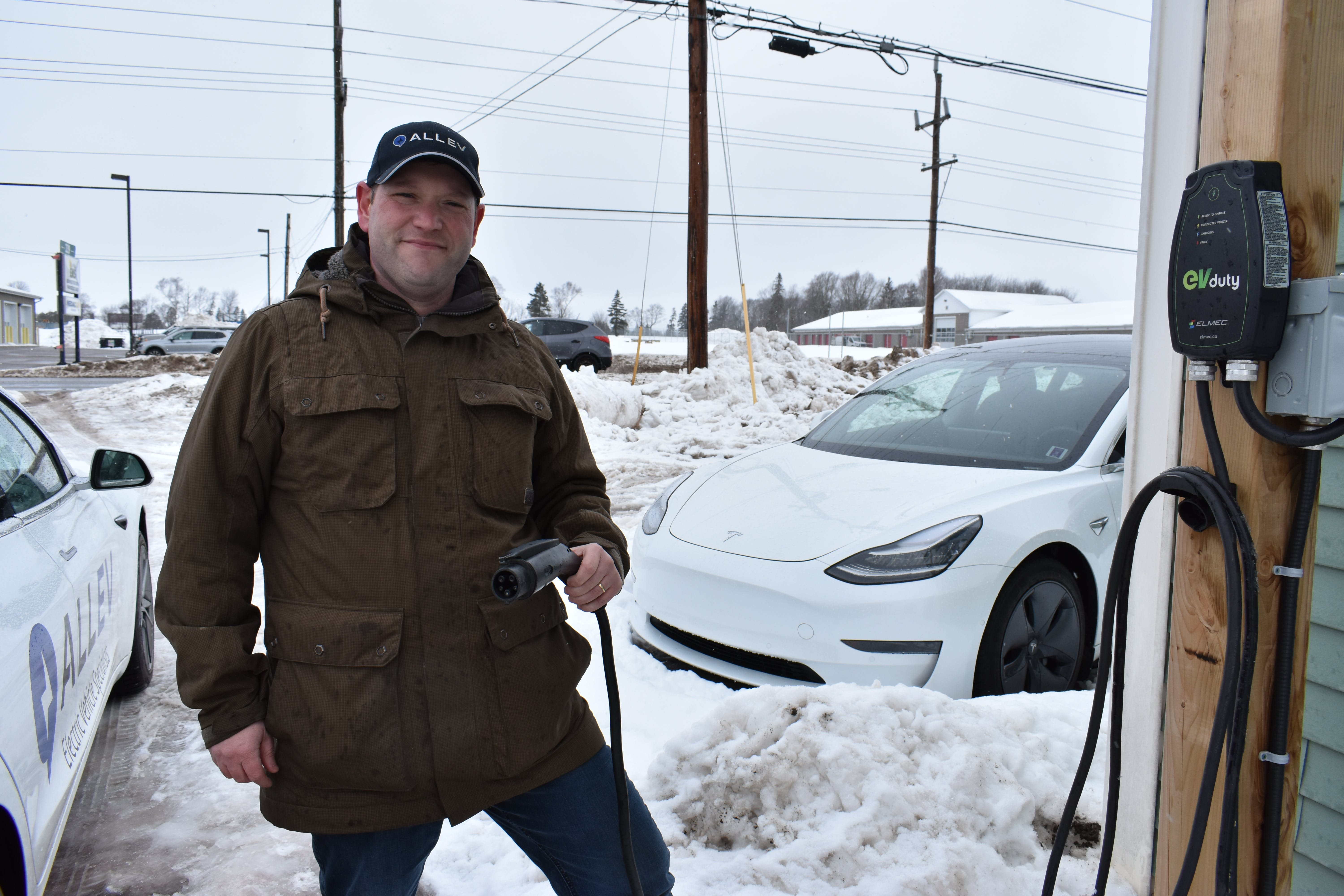 Mike Kenny, owner of the AllEV car dealership in Charlottetown, holds a charge cable attached to a Level 2 charger outside the dealership. By the end of the year, Maritime Electric says it will install 50 stations like it across the province.