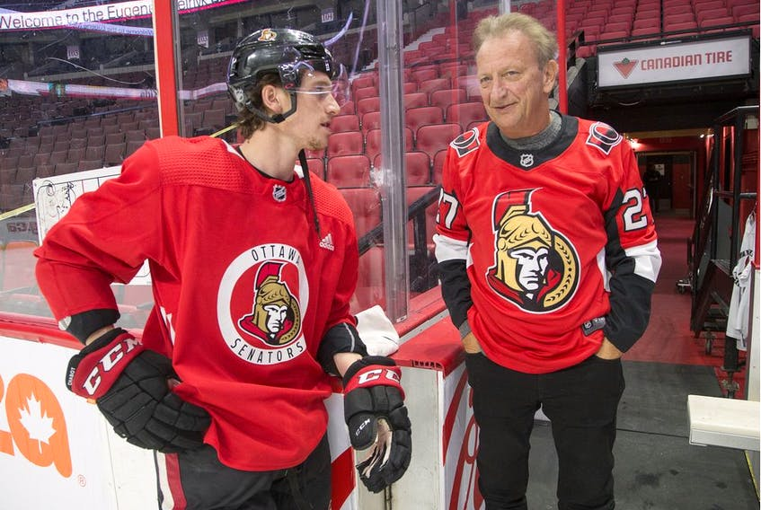 Senators owner Eugene Melnyk chats with defenceman Thomas Chabot, left, during the annual Eugene Melnyk Skate for Kids at Canadian Tire Centre on Dec. 20.