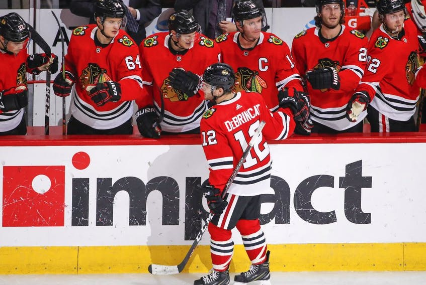Chicago Blackhawks left wing Alex DeBrincat (12) celebrates with teammates after scoring against the Edmonton Oilers during the second period at United Center.
