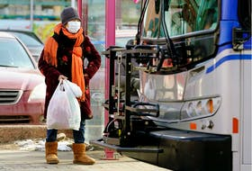 A woman, wearing a face mask for protection against COVID-19, waits to board a public bus in downtown Edmonton on March 17, 2020.