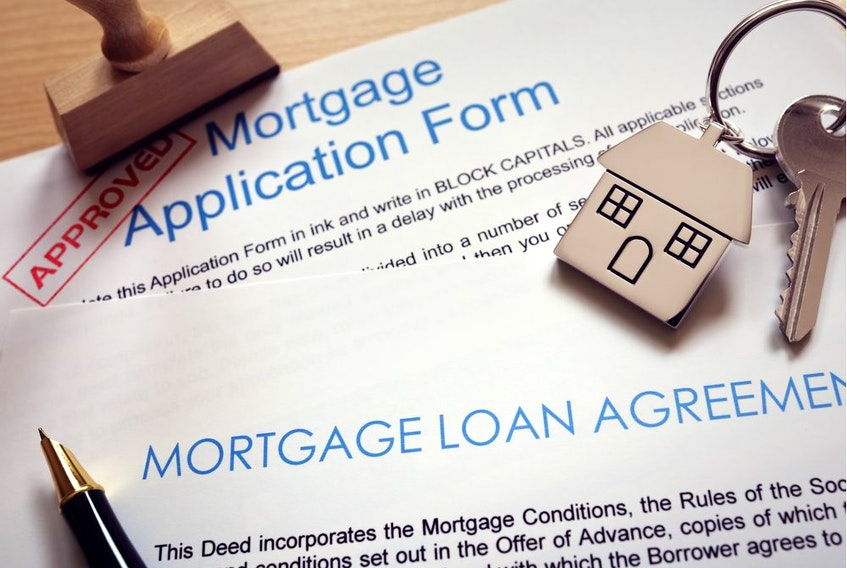 Mortgage loan agreement application with  key on house shaped keyring. Getty Images.