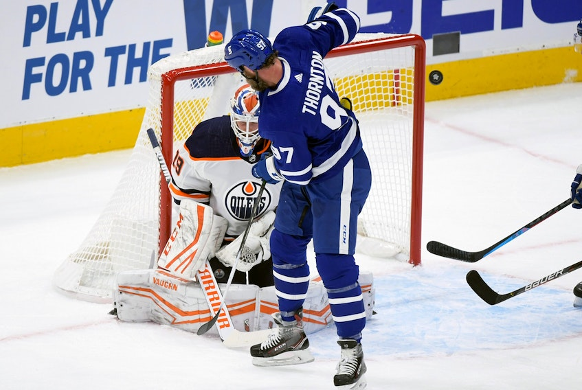 Toronto Maple Leafs forward Joe Thornton (97) deflects the puck and Edmonton Oilers goalie Mikko Koskinen (19) makes a save in the first period at Scotiabank Arena.
