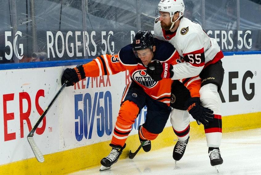 Edmonton Oilers' Jesse Puljujarvi (13) battles Ottawa Senators' Braydon Coburn (55) during first period NHL action at Rogers Place in Edmonton, on Tuesday, Feb. 2, 2021.