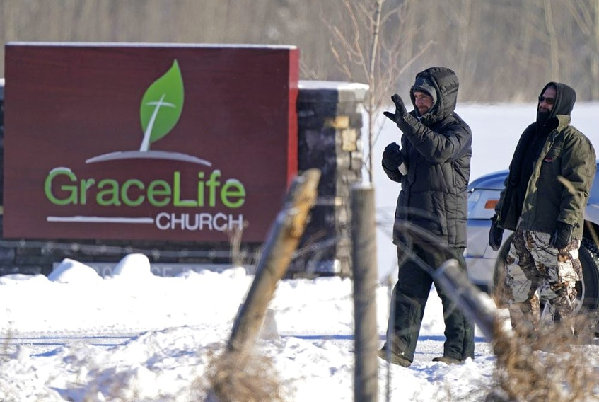Two men keep unwelcome visitors from entering the property at  GraceLife Church in Parkland County, just east of Edmonton, on Sunday February 7, 2021. The church has defied government pandemic restrictions multiple times and held a church service on this day.