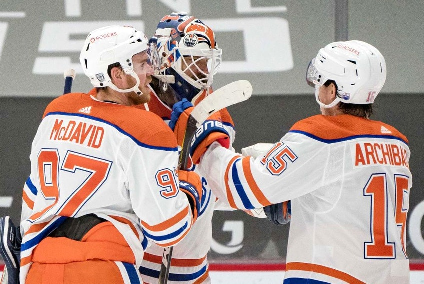 Edmonton Oilers forward Connor McDavid (97) and goalie Mike Smith (41) and forward  Josh Archibald (15) celebrate their victory against the Vancouver Canucks at Rogers Arena on Feb. 25, 2021.