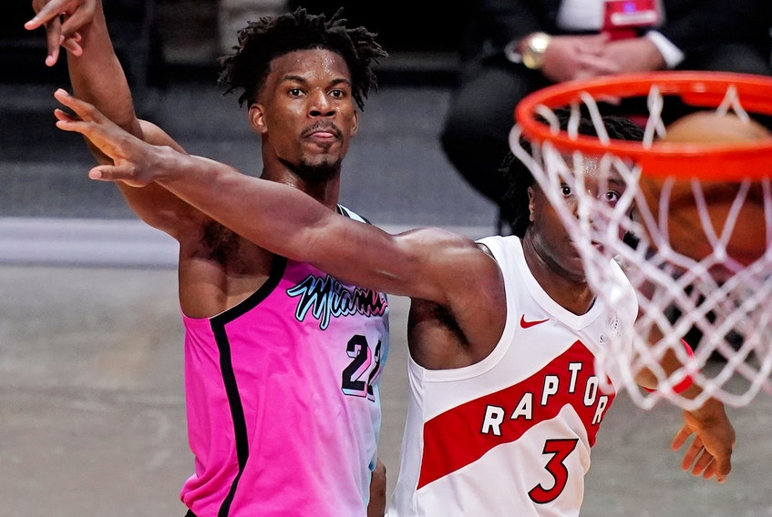 Heat forward Jimmy Butler (22) watches the ball into the net after shooting over Toronto Raptors forward OG Anunoby during the Heat's win on Wednesday.