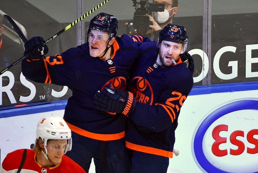 Edmonton Oilers Jesse Puljujarvi (13) celebrates his goal with Leon Draisaitl (29) against the Calgary Flames during NHL action at Rogers Place in Edmonton, March 6, 2021.