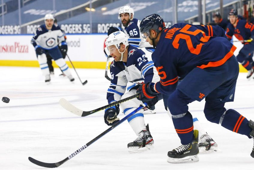 Oilers defensemen Darnell Nurse (25) chips the puck past Winnipeg Jets forward Trevor Lewis (23) during the second period at Rogers Place on March 20, 2021.