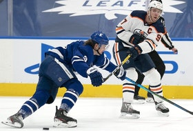 Edmonton Oilers center Connor McDavid (97) moves the puck against Toronto Maple Leafs defenseman Justin Holl (3) during the second period at Scotiabank Arena on March 27, 2021.